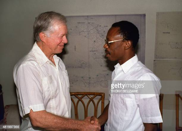 Former US President Jimmy Carter greets Haitian presidential candidate father JeanBertrand Aristide 15 December 1990 in PortauPrince on the eve of...