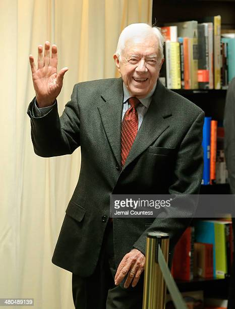 Former US President Jimmy Carter greets members of the press during an instore for his new book A Call To Action Women Religion Violence And Power at...