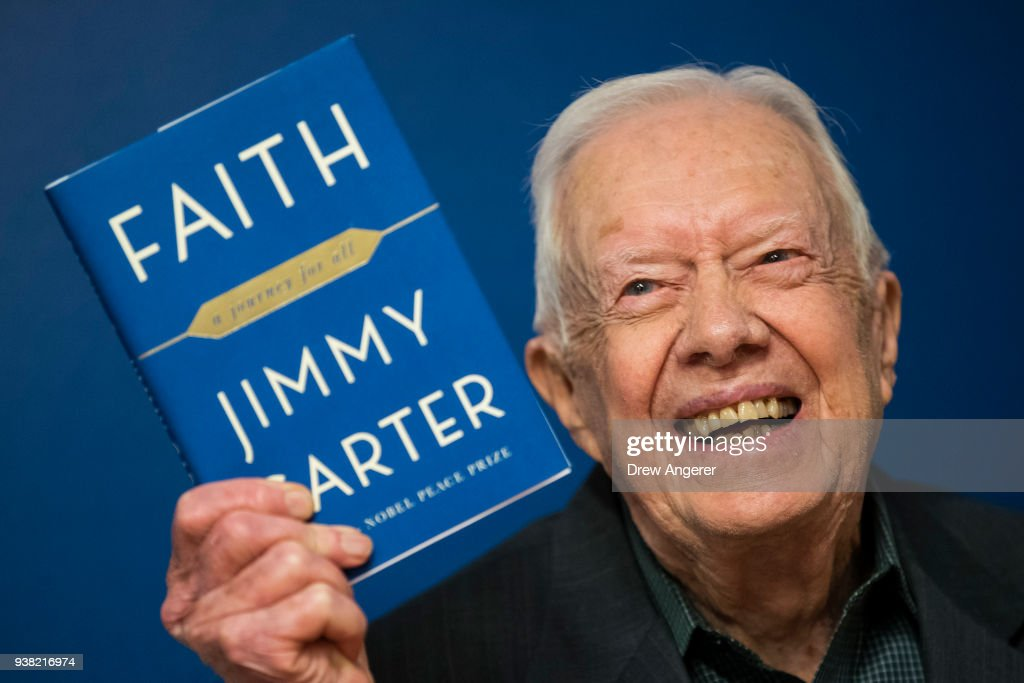 Former U.S. President Jimmy Carter holds up a copy of his new book 'Faith: A Journey For All' at a book signing event at Barnes & Noble bookstore in Midtown Manhattan, March 26, 2018 in New York City. Carter, 93, has been a prolific author since leaving office in 1981, publishing dozens of books.