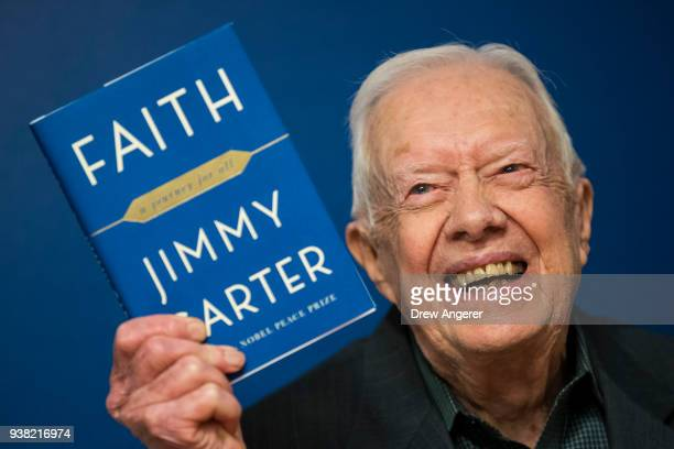 Former US President Jimmy Carter holds up a copy of his new book 'Faith A Journey For All' at a book signing event at Barnes Noble bookstore in...