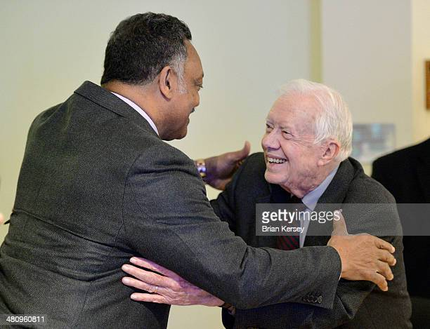 Former US President Jimmy Carter hugs Rev Jesse Jackson at a signing for his new book 'A Call to Action Women Religion Violence and Power' at Women...
