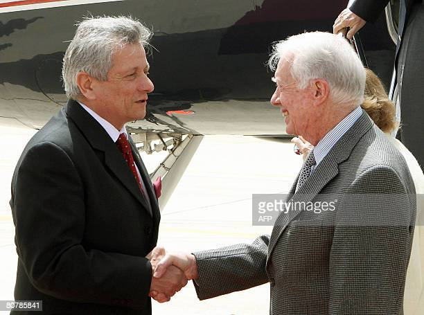 Former US president Jimmy Carter is greeted by Jordanian foreign ministry secretary general Khaldun Talhoni upon his arrival at Queen Alia...