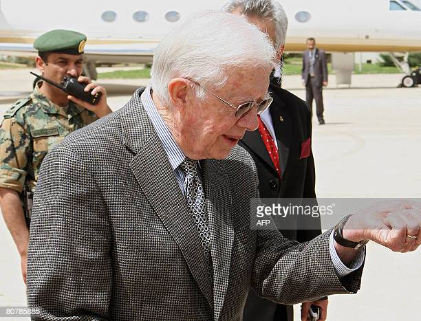 Former US president Jimmy Carter looks at his watch upon his arrival at Queen Alia international airport in Amman on April 20 2008 Carter arrived in...