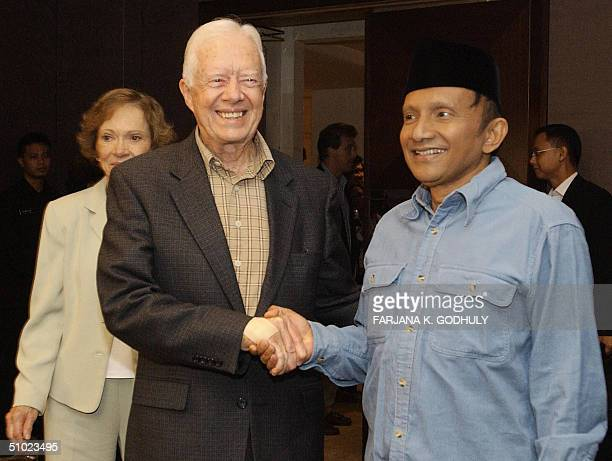 Former US president Jimmy Carter shakes hands with Indonesian presidential candidate Amien Rais following their private meeting in Jakarta 04 July...