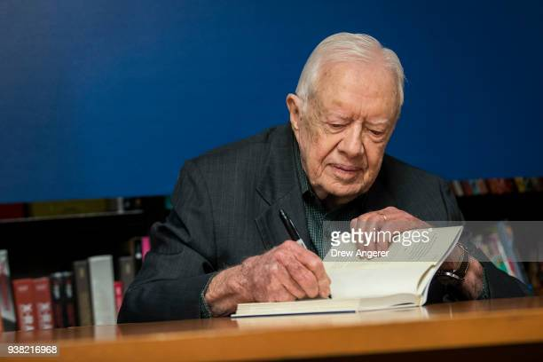 Former US President Jimmy Carter signs a copy of his new book 'Faith A Journey For All' at a book signing event at Barnes Noble bookstore in Midtown...