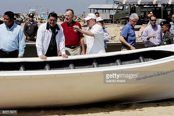 Former US presidents George Bush Senior and Bill Clinton inspect a fiber glass boat along with Thai Foreign Minister Surakiart Sathirathai during a...