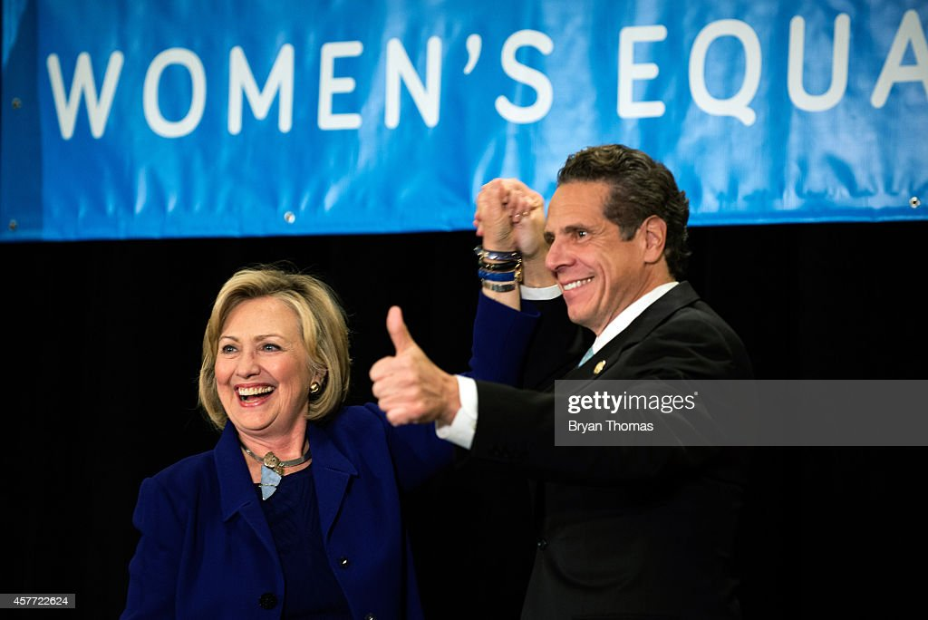 Former U.S. Secretary of State and U.S. Sen. Hillary Rodham Clinton (left to right) raises the hand of incumbent New York Governor Andrew Cuomo laugh during a 'Women for Cuomo' campaign event on October 23, 2014 at the Grand Hyatt Hotel in New York, NY. Cuomo was joined by Clinton who, citing his record on women's rights, endorsed him in the upcoming gubernatorial election on November 4, 2014. U.S. Rep. Kathy Hochul, the Democratic nominee for New York Lt. Gov., also spoke at the event.