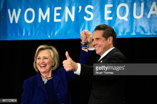 Former US Secretary of State and US Sen Hillary Rodham Clinton raises the hand of incumbent New York Governor Andrew Cuomo laugh during a 'Women for...
