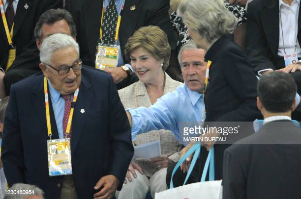 Former US Secretary of State Henry Kissinger takes a seat near US President George W. Bush and Laura Bush as they arrive at the National Aquatics...