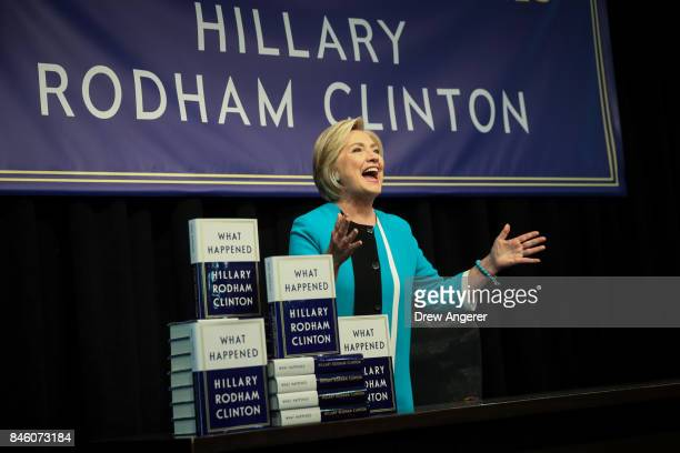 Former US Secretary of State Hillary Clinton acknowledges the audience as she arrives onstage to sign copies of her new book 'What Happened' during...