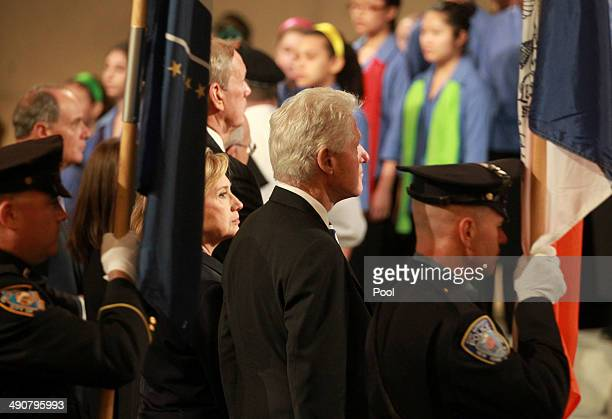 Former US Secretary of State Hillary Clinton and former US President Bill Clinton stand as the color guard processes during the dedication ceremony...
