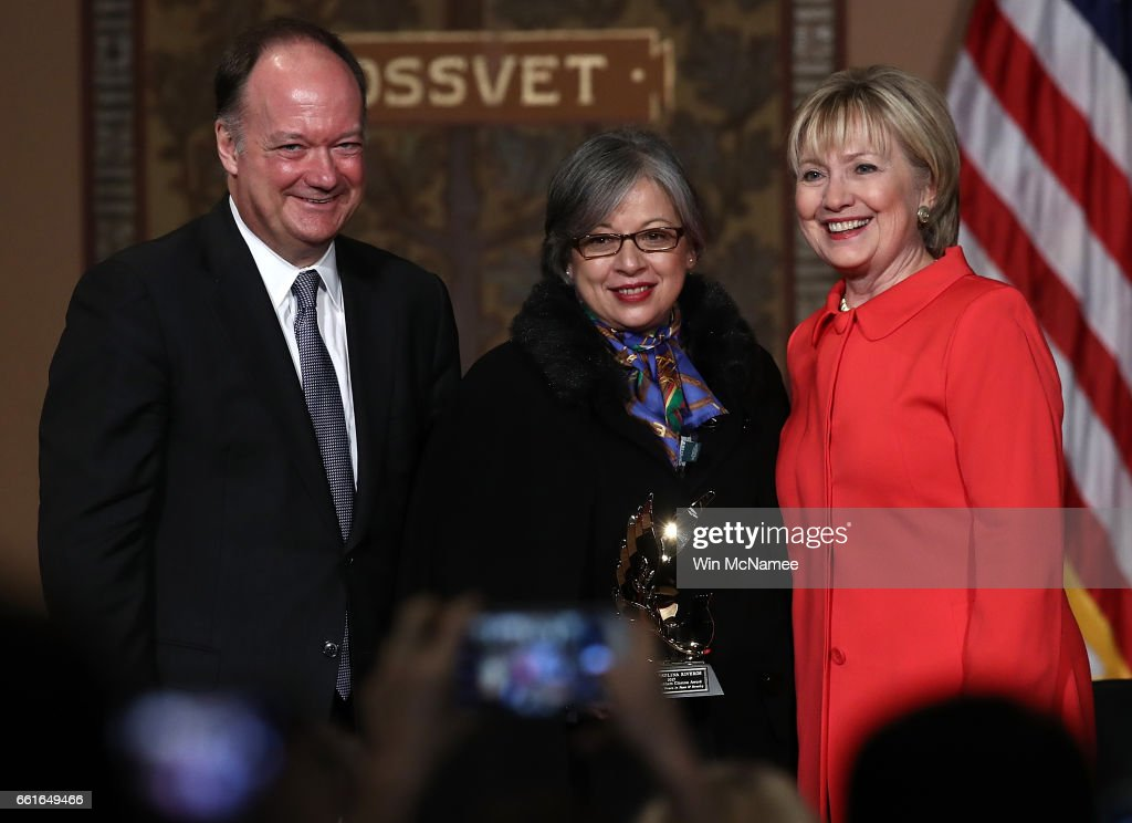 Former U.S. Secretary of State Hillary Clinton (R) greets Maria Paulina Riveros (C) after Riveros was presented the 2017 Hillary Rodham Clinton Award for Advancing Women in Peace and at Georgetown University March 31, 2017 in Washington, DC. Clinton spoke before presenting the ceremony hosted by the Georgetown Institute for Women, Peace and Security. Also pictured is Georgetown University President Joe DeGioia (L).