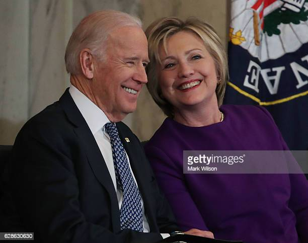 Former US Secretary of State Hillary Clinton shares a laugh with US Vice President Joseph Biden during a portrait unveiling ceremony for outgoing...