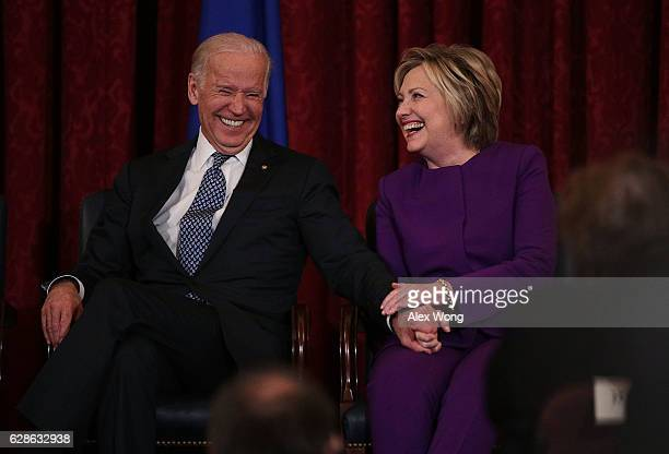 Former US Secretary of State Hillary Clinton shares a moment with Vice President Joseph Biden during a leadership portrait unveiling ceremony for...