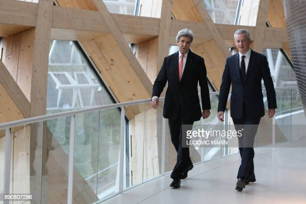 Former US secretary of state John Kerry and French Minister of Economy and Finance Bruno Le Maire walk during the One Planet Summit on December 12...