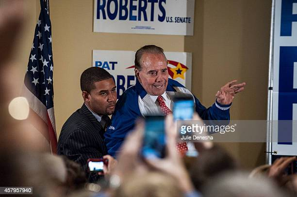 Former US Sen Bob Dole of Kansas is assisted to the stage during a rally for US Sen Pat Roberts at the Prairie Fire shopping center October 27 2014...