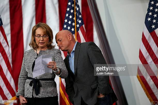 Former US Sen Gabrielle Giffords reads from notes as her husband US Navy captain Mark Kelly looks on during a get out the caucus event for democratic...