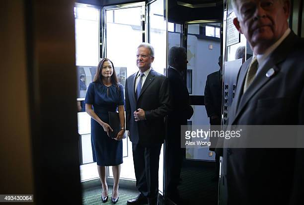 Former US Sen Jim Webb and his wife Hong Le Webb leave after a news conference at the National Press Club October 20 2015 in Washington DC Sen Webb...