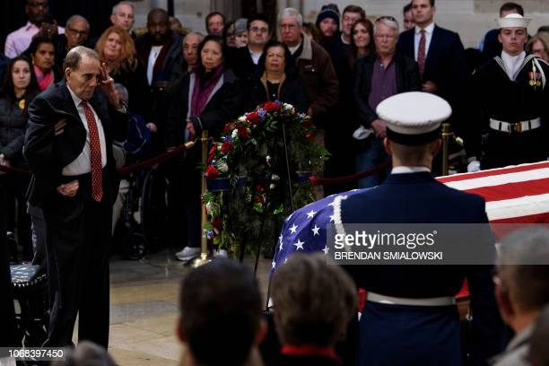 Former US Senator Bob Dole salutes before the flagdraped coffin of former US President George H W Bush at the US Capitol rotunda December 4 2018 in...