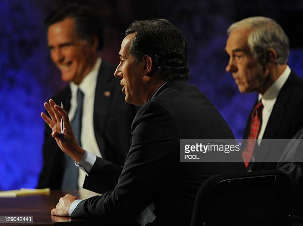 Former US senator rick Santorum makes a point as former Massachusetts governor Mitt Romney and Texas Rep Ron Paul listen during a presidential debate...