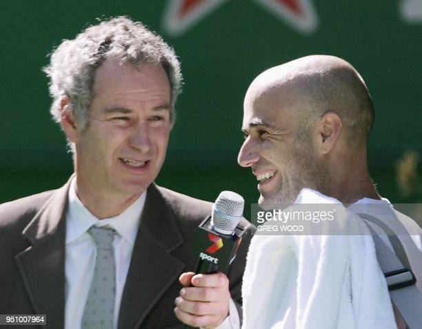 Former US tennis great John McEnroe conducts a postmatch interview with second seeded Andre Agassi of the US following his victory over Sebastien...