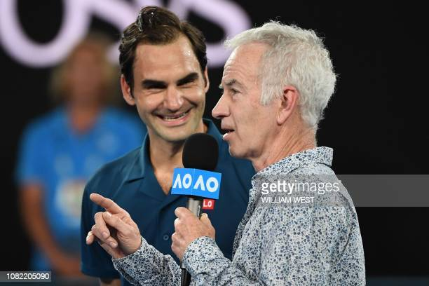 Former US tennis player John McEnroe interviews Switzerland's Roger Federer after his victory against Uzbekistan's Denis Istomin after their men's...