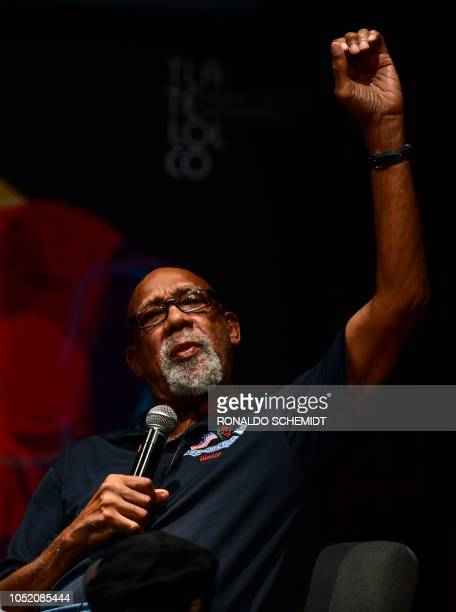 Former US track and field athlete and professional football player John Carlos, raises his fist as he speaks during a conference at the National...