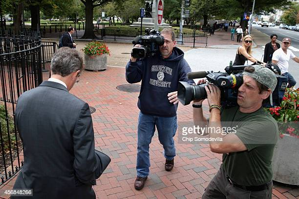 Former US Treasury Secretary Timothy Geithner is followed by television cameramen after leaving the US Court of Federal Claims during a lunch break...