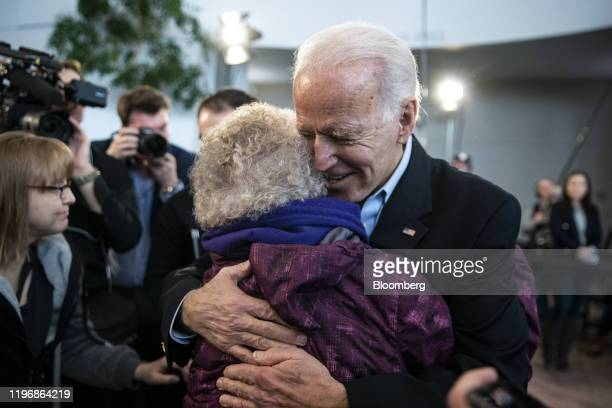 Former US Vice President Joe Biden 2020 Democratic presidential candidate hugs an attendee during a campaign event in Cedar Falls Iowa US on Monday...