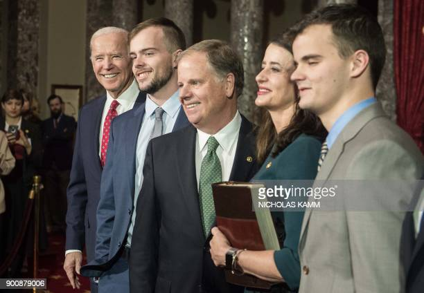 Former US vice president Joe Biden looks as he poses for a picture with new Democratic Senator from Alabama Doug Jones his wife Luise and sons Carson...