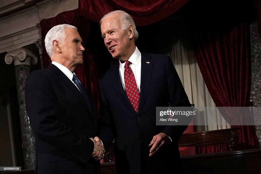 Former U.S. Vice President Joseph Biden (R) and incumbent U.S. Vice President Mike Pence (L) share a moment during a mock swearing-in ceremony for U.S. Sen. Doug Jones (D-AL) at the Old Senate Chamber of the U.S. Capitol January 3, 2018 in Washington, DC. Jones is the first Democratic senator from Alabama in more than two decades. He defeated Roy Moore leaving Republicans with a 51-49 majority in the U.S. Senate.