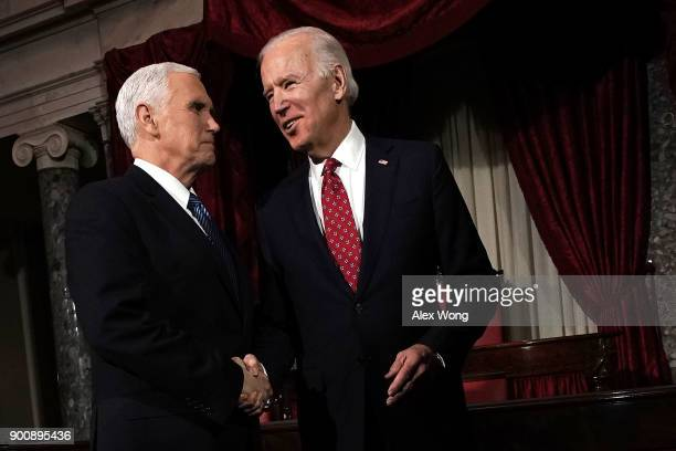 Former US Vice President Joseph Biden and incumbent US Vice President Mike Pence share a moment during a mock swearingin ceremony for US Sen Doug...