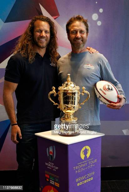Former USA Eagles captain Todd Clever and Gerard Butler pose for photos with The Webb Ellis Cup during day two of the Rugby World Cup 2019 Trophy...