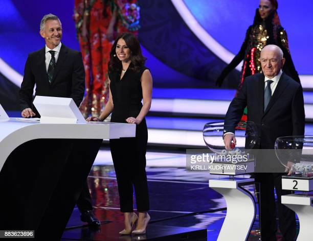 Former USSR forward and coach Nikita Simonyan picks up the red 'Russia' ball next to Russian sports journalist and draw conductor Maria Komandnaya...
