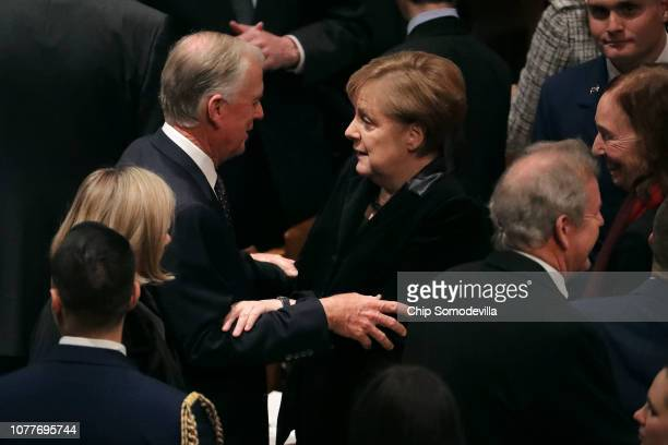 Former Vice President Dan Quayle greets German Chancellor Angela Merkel during the state funeral for former President George HW Bush at the National...