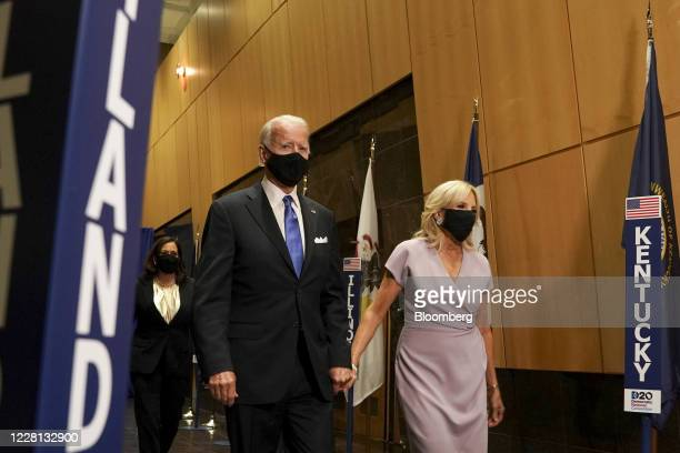 Former Vice President Joe Biden, Democratic presidential nominee, left, and wife Jill Biden wear protective masks while exiting Chase Center during...