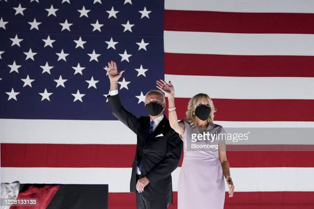 Former Vice President Joe Biden, Democratic presidential nominee, left, and wife Jill Biden wear protective masks while waving outside the Chase...