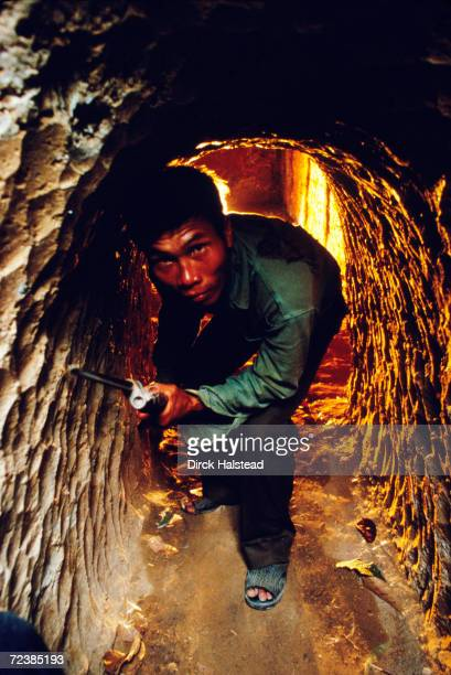 Former Viet Cong soldier inside tunnels he used during the Vietnam War and through which he now leads tour groups