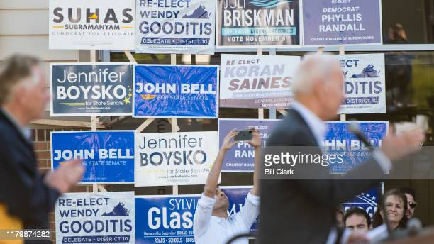 Former Virginia Gov Terry McAuliffe left claps as former Vice President Joe Biden speaks in front of a wall of campaign signs during a canvass kick...