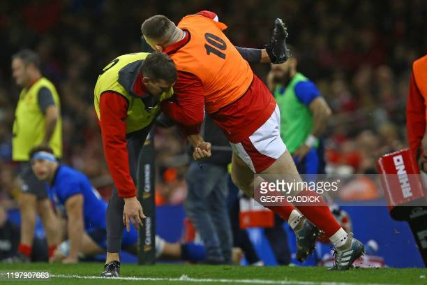 Former Wales captain, now assistant coach Sam Warburton helps Wales' prop Rob Evans warm up on the touchline during the Six Nations international...