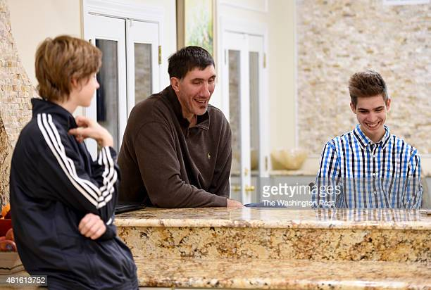 Former Washington Bullets center Gheorghe Muresan talks with his sons Victor and George at their home on January 8, 2015 in Potomac, MD.