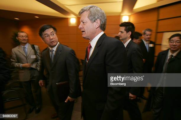 Former Washington Governor Gary Locke left talks to Senate Finance Committee Chairman Max Baucus a Montana Democrat after delivering the keynote...