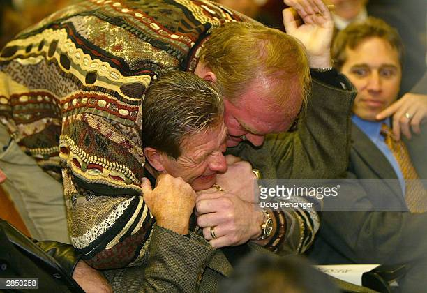 Former Washington Redskins defensive lineman Joe Jacoby wrestles with coach Joe Bugel as they await Joe Gibbs to address the media on January 8 2004...