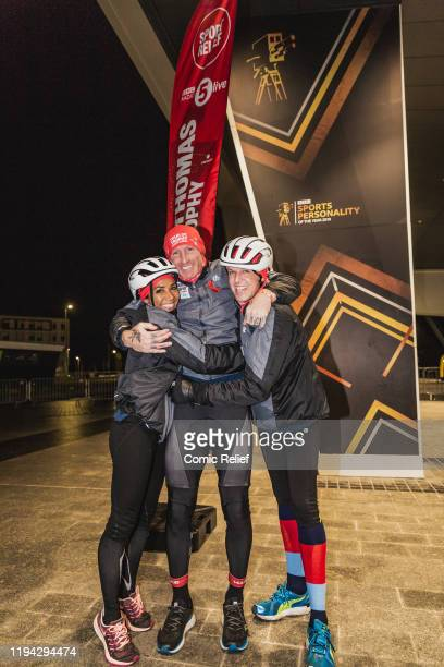Former Welsh, and British and Irish Lions, rugby captain Gareth Thomas hugs Dame Kelly Holmes and Graeme Swann as he completes Day 7 of the Tour De...