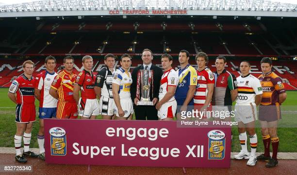 Former Welsh International player Scott Quinnell holds the trophy as he lines up with team captains Hull KR's James Webster, Wakefield Trinity...