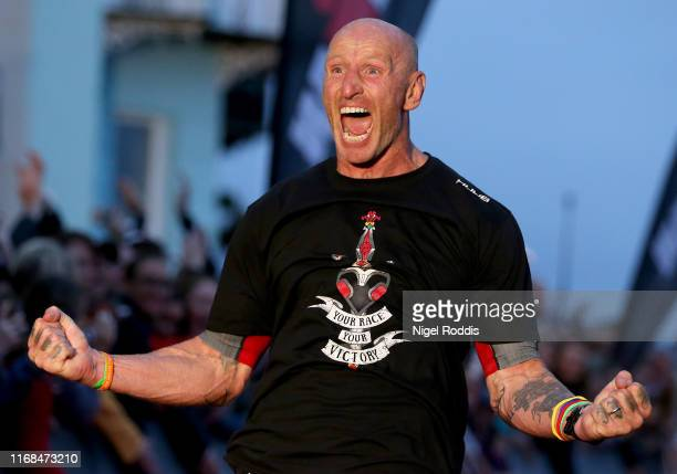 Former Welsh rugby International captain Gareth Thomas reacts after finishing Ironman Wales on September 15, 2019 in Tenby, Wales.