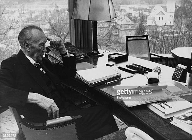 Former West German Chancellor Konrad Adenauer sitting at a desk holding the transcript of his autobiography on the eve of his eightyninth birthday
