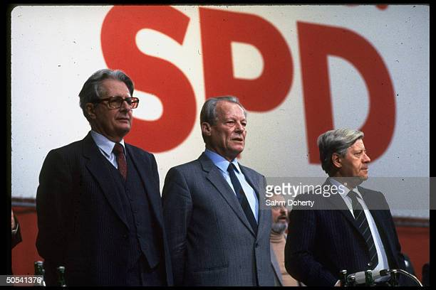 Former West German Chancellors Helmut Schmidt and Willy Brandt standing with Chancellor candidate Hans Jochen Vogel at Social Democratic Party...