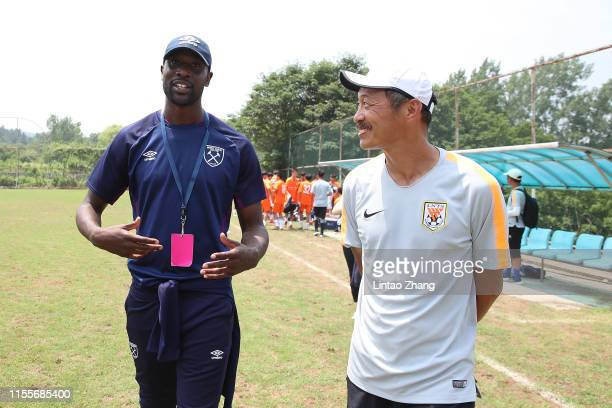 Former West Ham player Carlton Cole talk with Kurata Yasuharu head coach of Shangdong Luneng guide young players during the CSL Cup Youth Tournament...