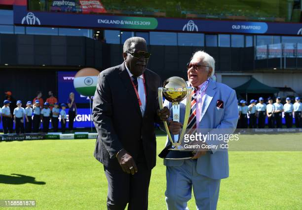Former West Indies Cricketer Clive Lloyd and Former India Cricketer Farokh Engineer carry out the trophy prior to the national anthems during the...